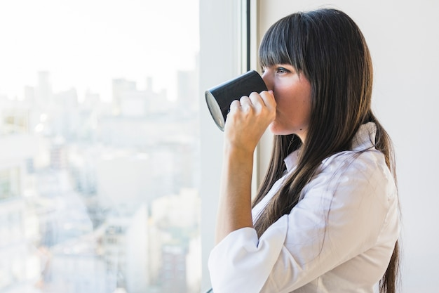 Woman standing near the window drinking coffee Free Photo