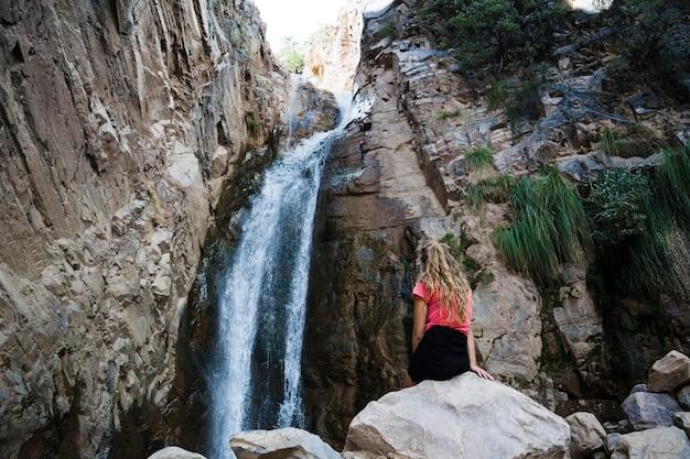 Woman standing near waterfall Free Photo