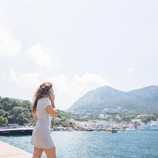 携帯電話で話している桟橋に立っている女性 無料写真