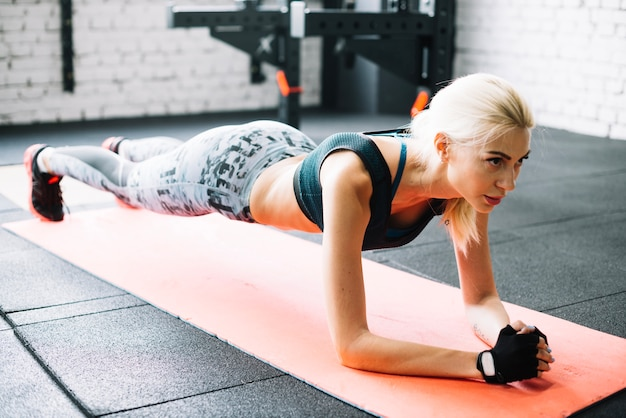 Woman standing in plank position Free Photo
