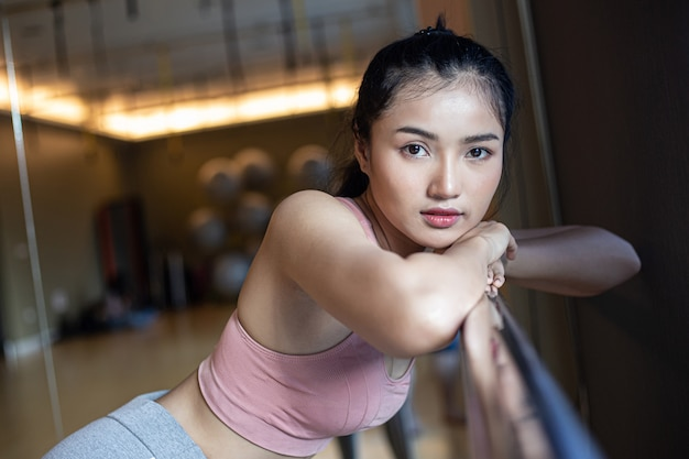 A woman standing relaxed, hands placed on a steel rail in the gym. Free Photo