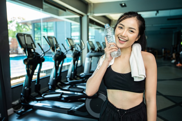 Woman standing and relaxing after exercising, holding a bottle of water to touch the face. Free Photo