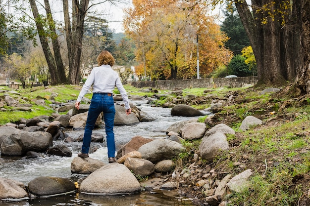 Woman standing on river rocks Free Photo