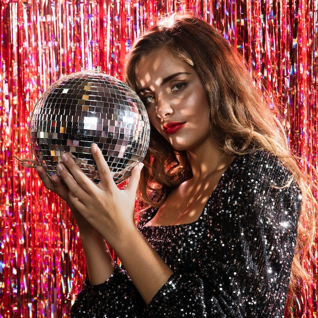 Woman standing side view holding a disco ball Free Photo