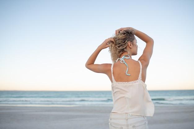 Женщина, стоящая с руками в ее волосы на пляже Бесплатные Фотографии