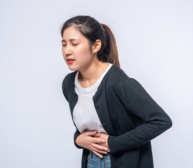 A woman standing with a stomach ache and presses her hand on her stomach. Free Photo