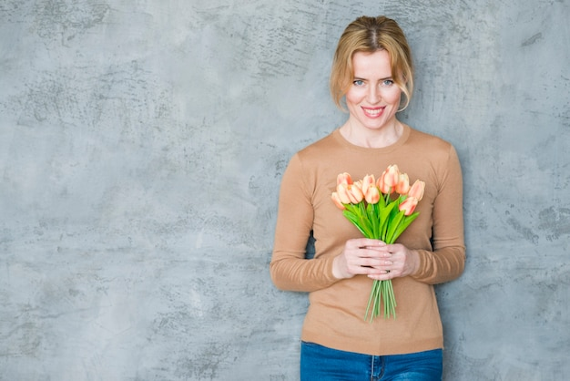 Woman standing with tulips bouquet Free Photo