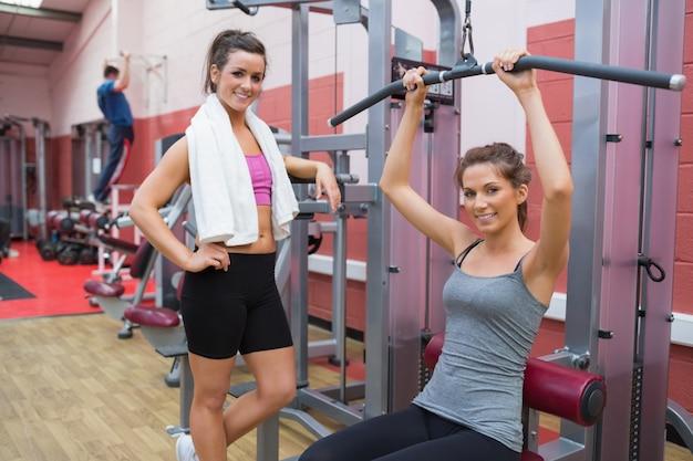 Woman stands beside friend using weights machine Premium Photo