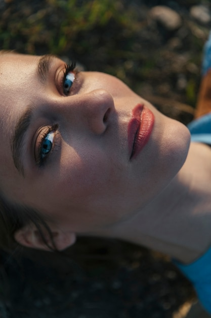 明るい顔と青い目を持つカメラを見つめて女性 無料写真