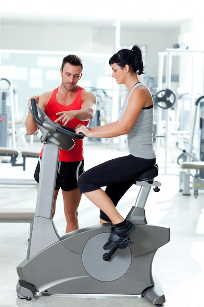 Woman on stationary bicycle with personal trainer Premium Photo