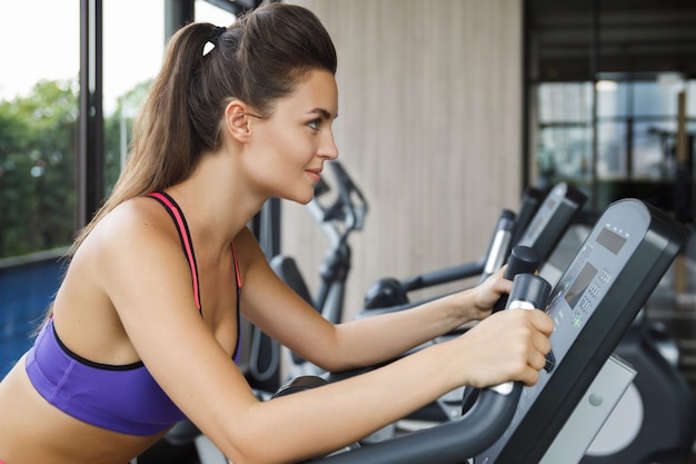 Woman on stationary bike in the gym Premium Photo