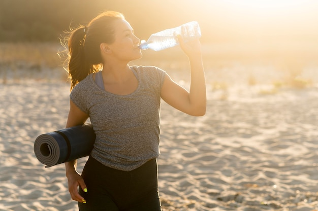 Woman staying hydrated while exercising on the beach Free Photo