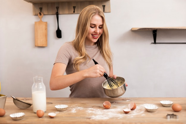 Woman stir the eggs and milk in the metallic bowl Free Photo
