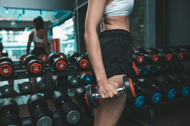 The woman stood holding a dumbbell at the thigh in the gym. Free Photo