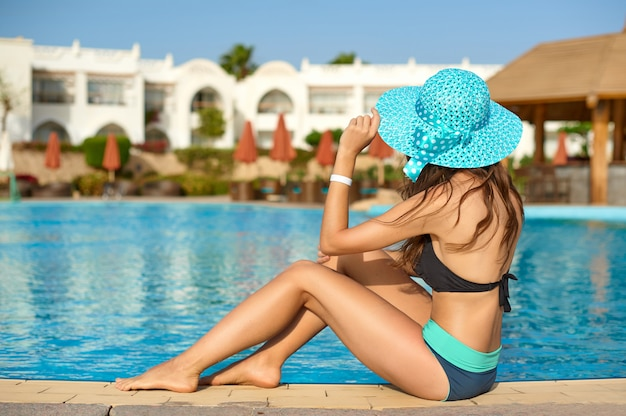 Woman in a straw hat relaxing on a deck-chair near a luxurious summer pool in hotel, concept time to travel Premium Photo