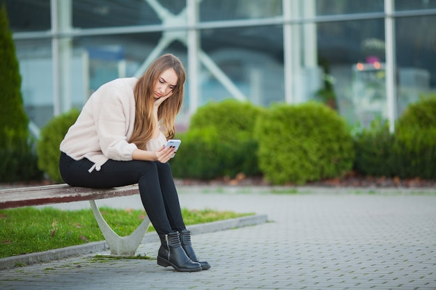 Woman stressed from work while sitting outdoors, press from colleagues Premium Photo
