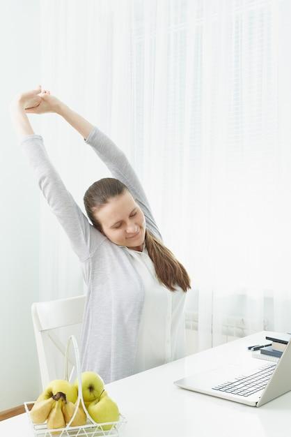 女性は腕を伸ばし、疲労から背中をこねます。 Premium写真