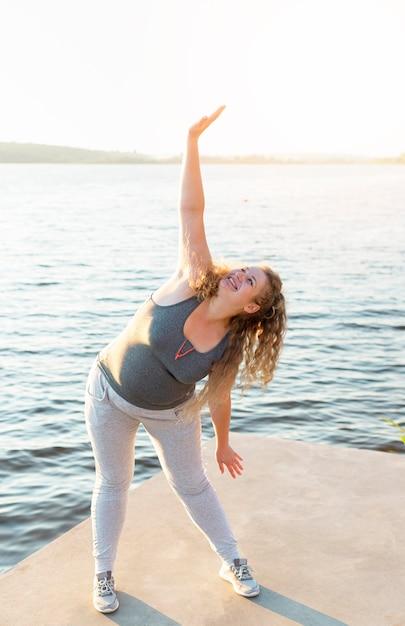 Женщина растягивается на берегу озера Бесплатные Фотографии