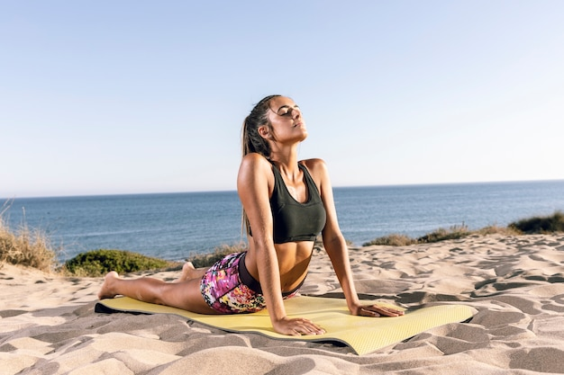 Woman stretching her back on fitness mat Free Photo