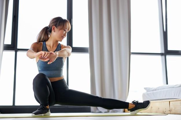 ヨガの前に足を伸ばしたり、マットの上でエクササイズをしたり、トレーニングをしたりする女性。健康的なライフスタイルとスポーツの概念 Premium写真