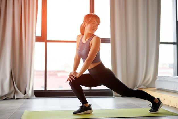 足を伸ばし、自宅でトレーニングする女性。フィットネス、トレーニング、瞑想、ヨガ、セルフケア、ピラティス、健康的なライフスタイルのコンセプト Premium写真