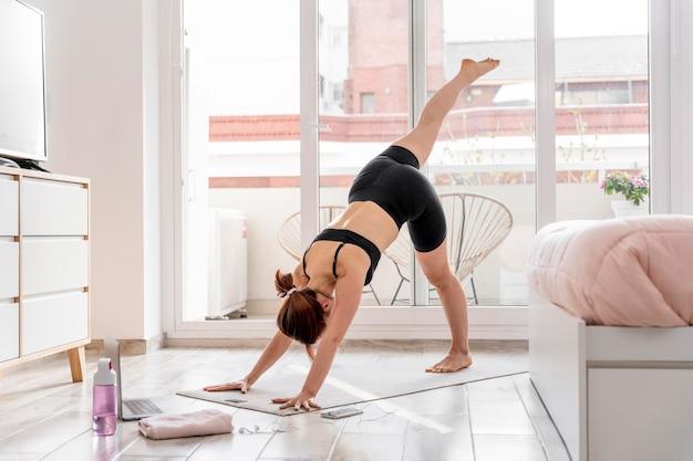 Женщина, растягивающаяся на коврике для йоги Бесплатные Фотографии
