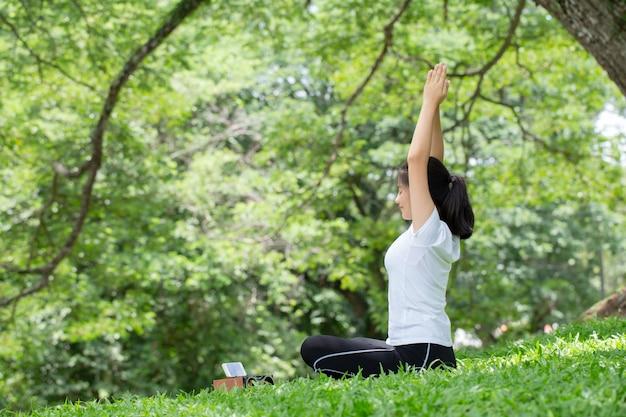 自然の中でヨガのポーズで自分を伸ばす女性。健康の概念。 Premium写真