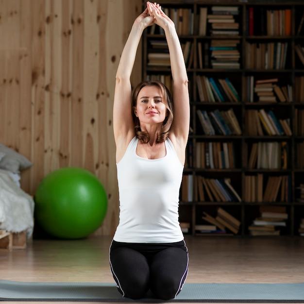 Woman stretching on yoga mat Free Photo