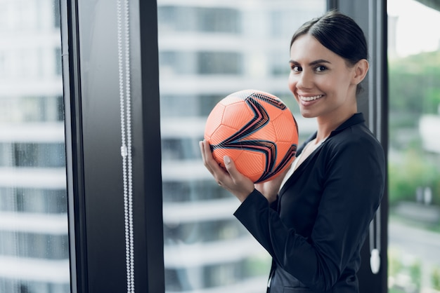 A woman in a strict business suit holds an orange football. Premium Photo