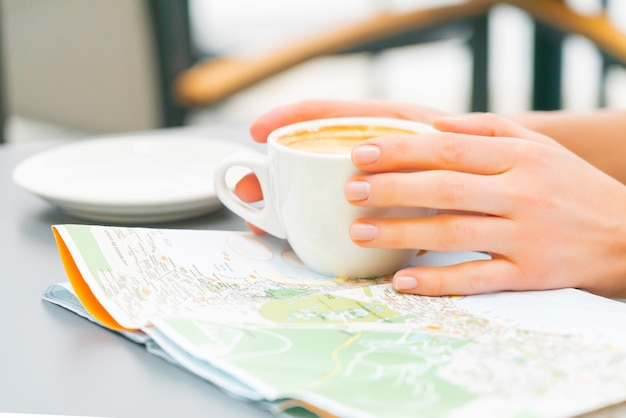 ストリートカフェでコーヒーを飲む女性研究マップ。赤毛の幸せな女の子旅行カナリア諸島と訪問する新しい場所を探しています。晴れた日。 無料写真