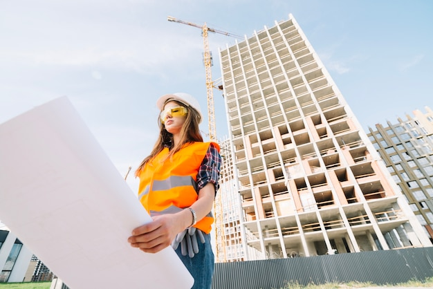 Woman studying draft on construction site Free Photo