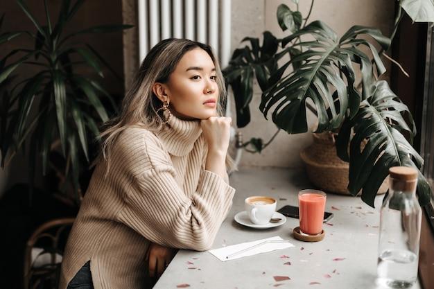 Donna in elegante maglione beige guarda pensieroso in lontananza, appoggiato sul tavolo con una tazza di caffè e succo di frutta fresco Foto Gratuite