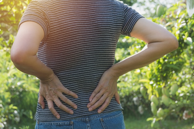 A woman suffering from backache, spinal injury and muscle issue problem at outdoor. Premium Photo