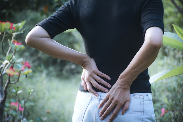 A woman suffering from backache, spinal injury and muscle issue problem Premium Photo