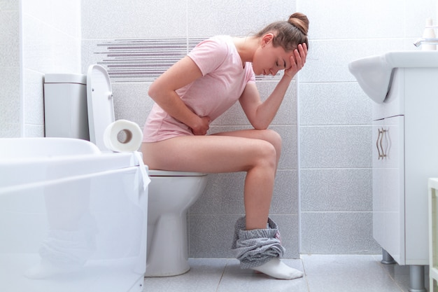 Woman suffering from diarrhea, constipation and stomach pain at toilet. treatment abdominal pain and food poisoning. health care Premium Photo