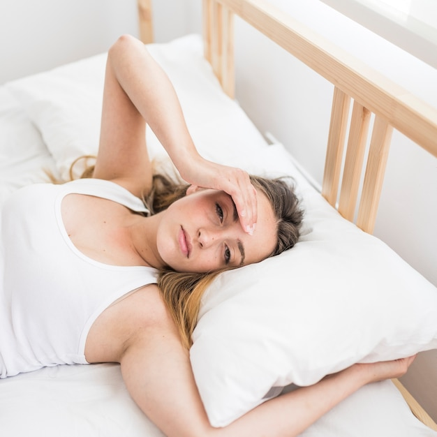 Woman suffering from headache lying on bed Free Photo