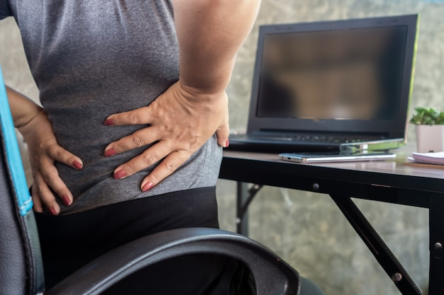 Woman suffering from office syndrome having lower back pain Premium Photo