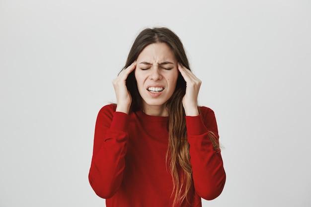 片頭痛に苦しんでいる女性、こめかみをこすり、目を閉じて顔をしかめ、頭痛を感じる 無料写真