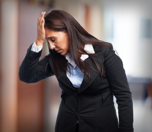 Woman in suit with headache Free Photo