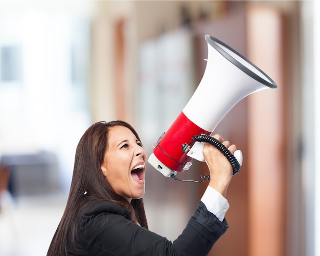 Woman in suit yelling through a megaphone Free Photo