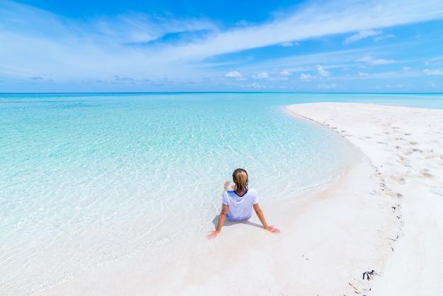 Woman sunbathing on scenic white sand beach, rear view, sunny day, turquoise transparent water, real people. indonesia, wakatobi islands Premium Photo