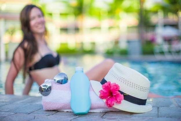 Woman, suncream, hat, sunglasses, flower and tower near swimming pool Premium Photo