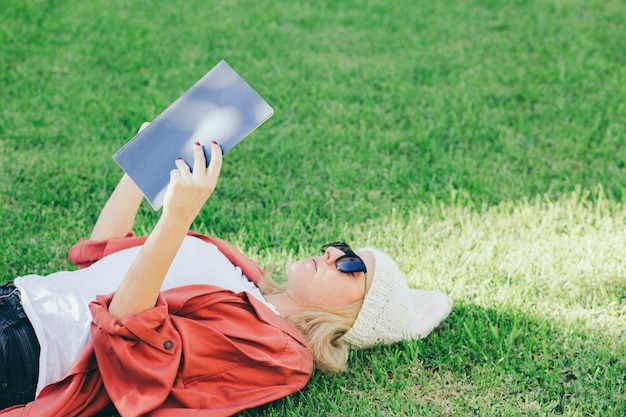 Woman in sunglasses reading book on lawn Free Photo