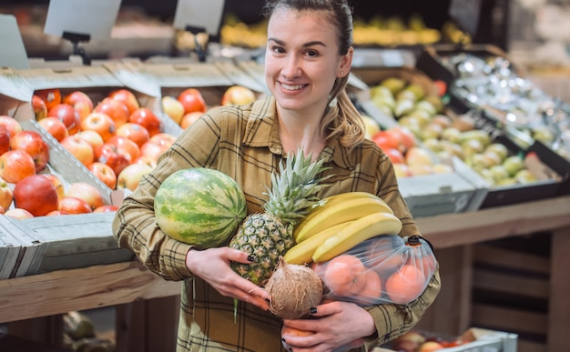 Woman in the supermarket. beautiful young woman shopping in a supermarket and buying fresh organic vegetables Free Photo