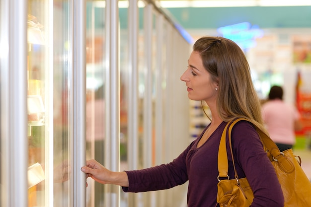 Woman in supermarket freezer section Premium Photo
