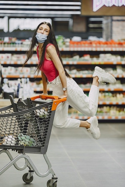 Woman in a supermarket. lady in a respirator. girl makes parchases. Free Photo