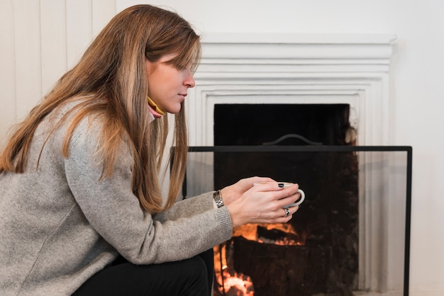 Woman in sweater drinking tea near fireplace Free Photo