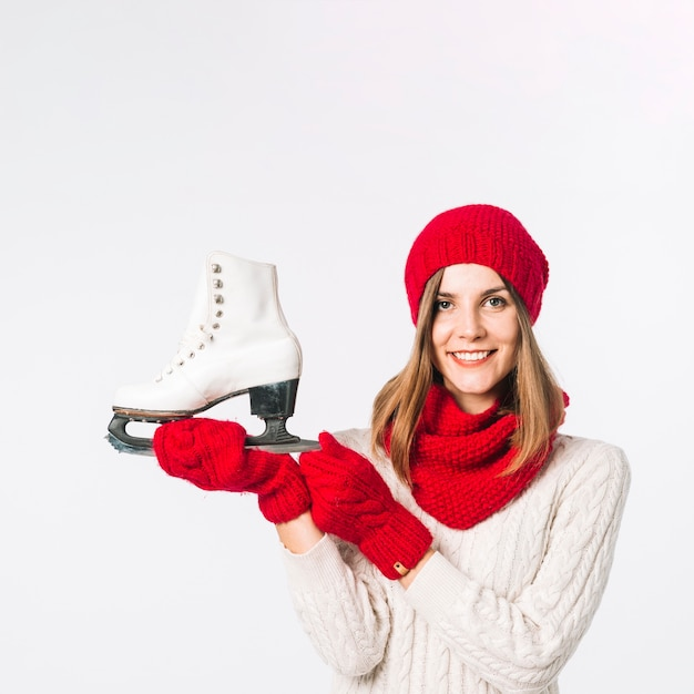 Woman in sweater holding skate Free Photo
