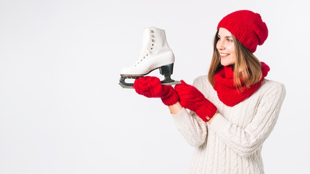 Woman in sweater holding white skate Free Photo