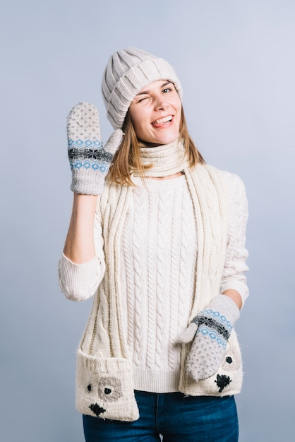 Woman in sweater showing greeting gesture Free Photo